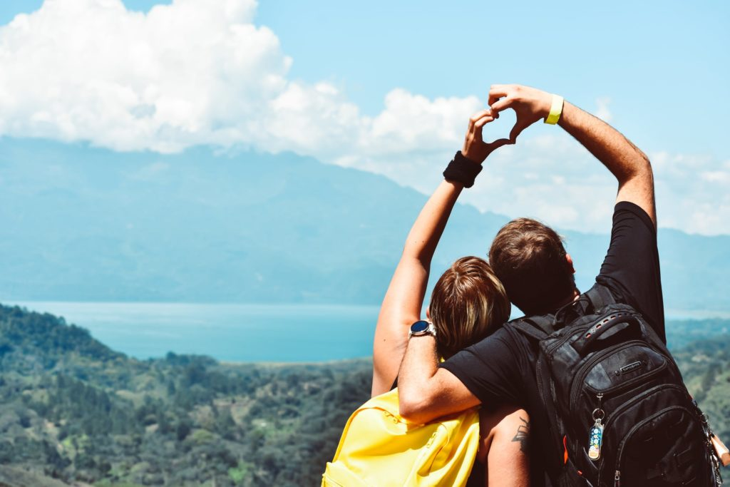 Couple making a love shape with theirs hands on a mountain having a weekend break