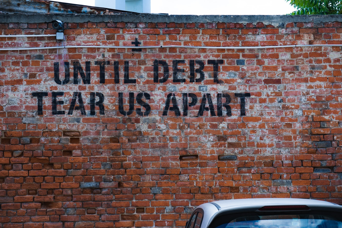 Brick wall with the word Until Debt Tear Us Apart written on it in black paint - finance