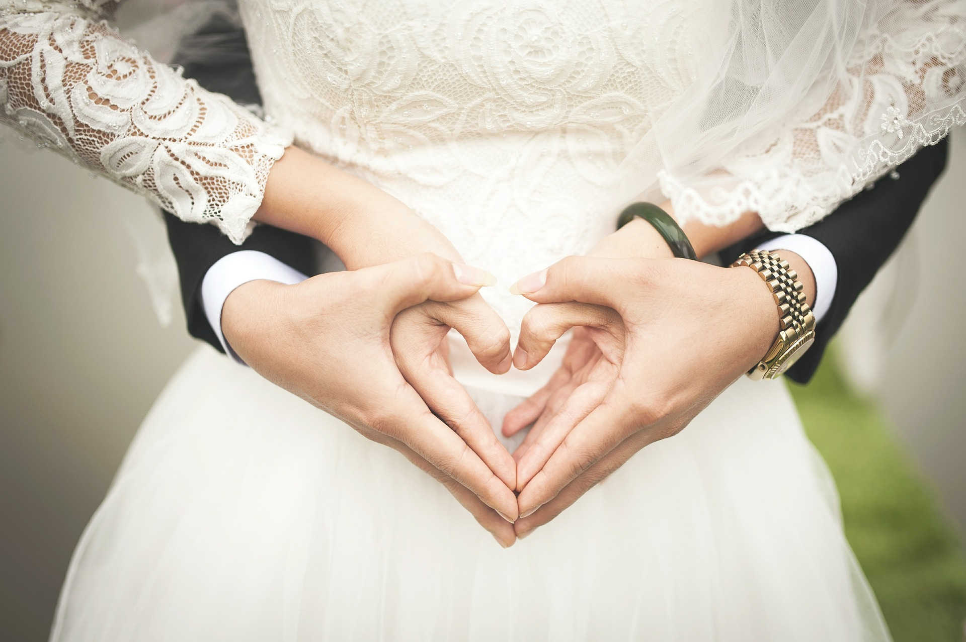 Groom standing behind bride making love heart shape with their hands - wedding day